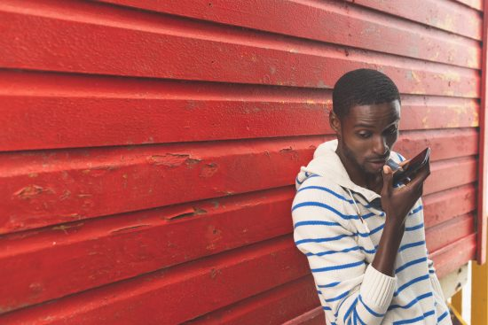 Young guy talking into smartphone against red fence