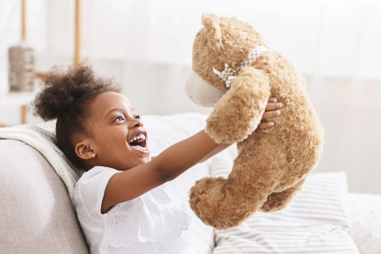 Young girl playing with teddy bear