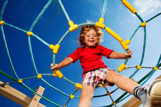 Young boy climbing spider climbing frame