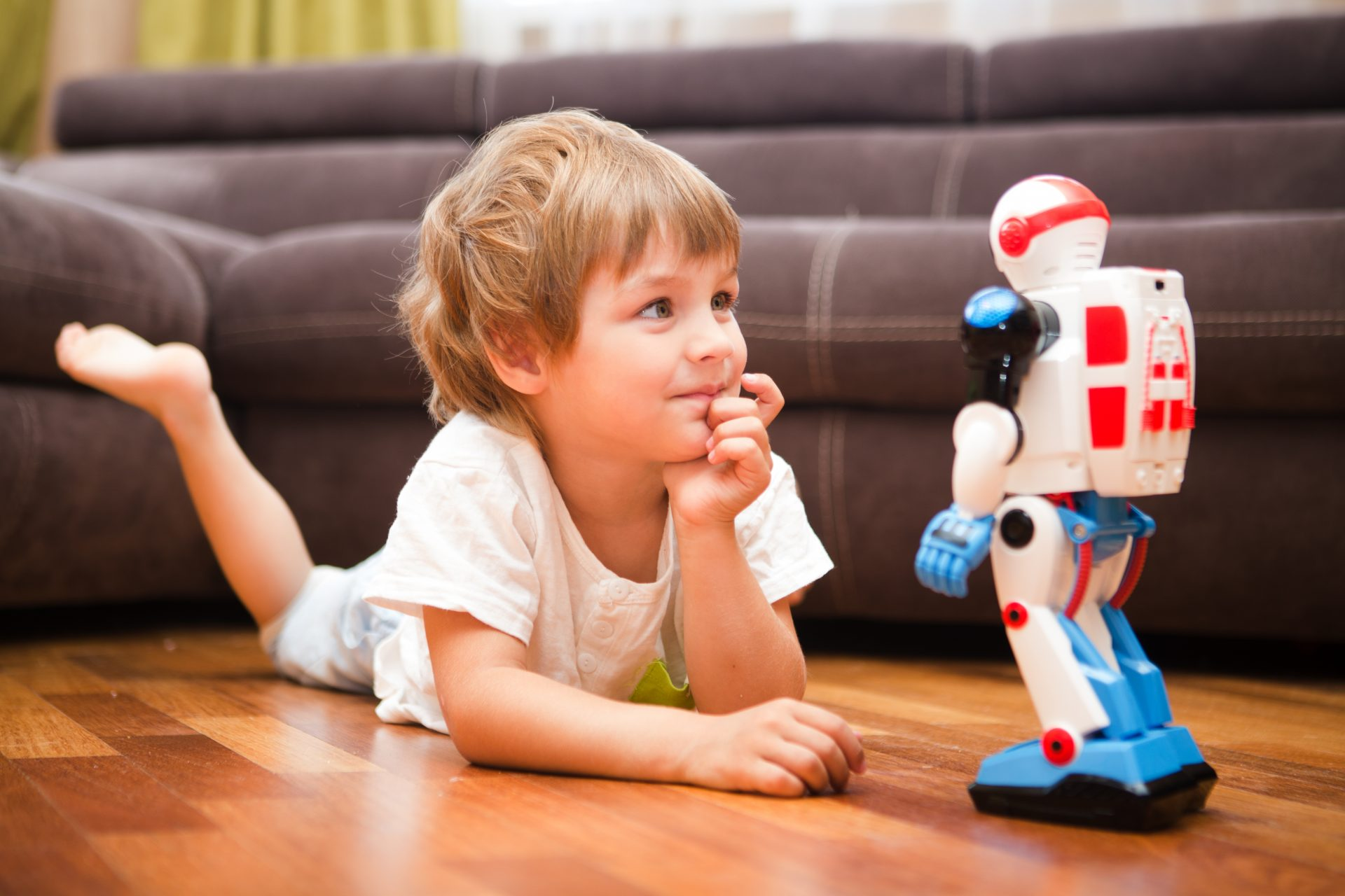 Young boy lying on floor staring at toy robot