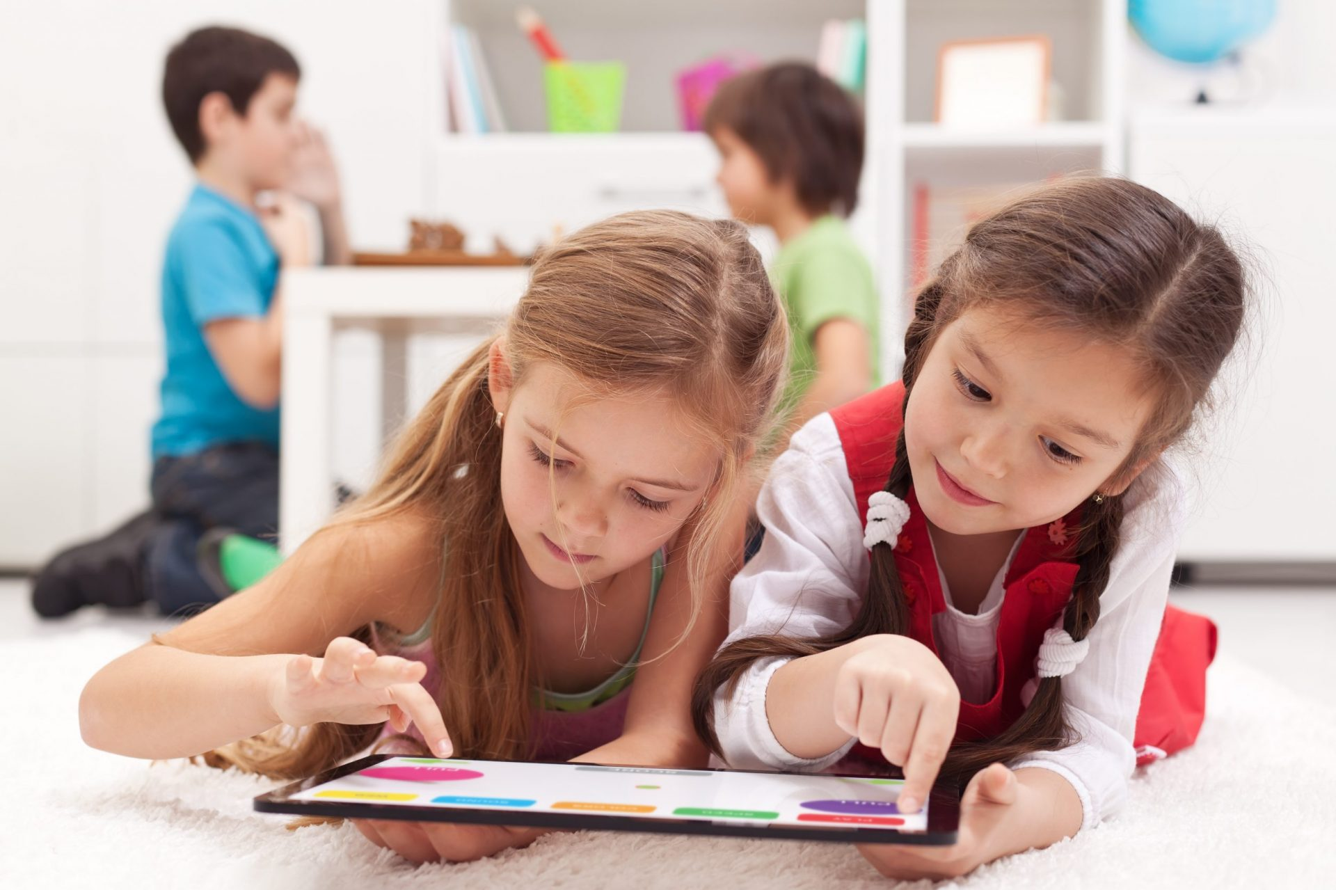 Back to school: Two little girls sharing a tablet computer