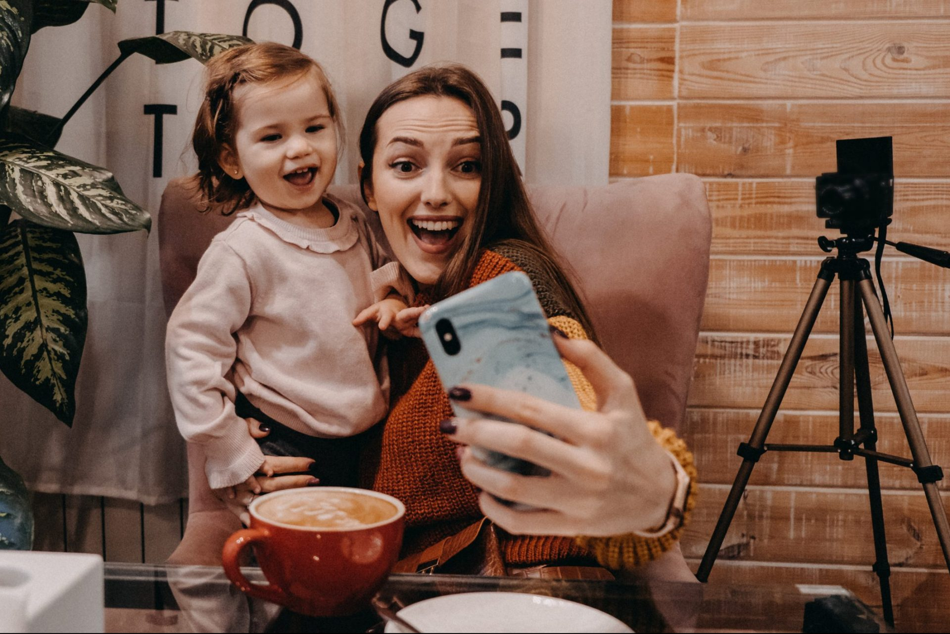 Young parent taking selfie with young child